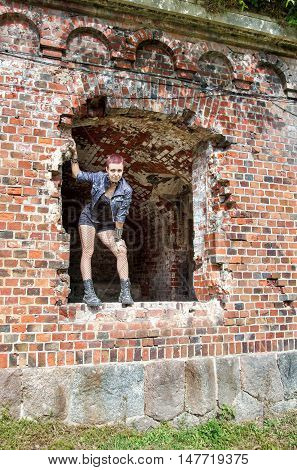 punk girl standing in the window of hte abandoned castle