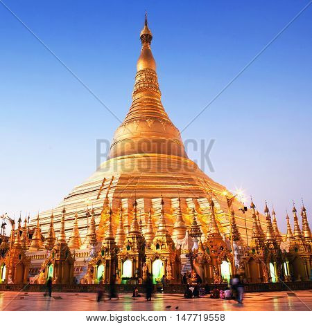 YANGON, MYANMAR - JANUARY 26, 2011: Pilgrims walking around golden Shwedagon Pagoda at sunrise in Yangon Myanmar. The pagoda is situated on Singuttara Hill and dominates the Yangon skyline.