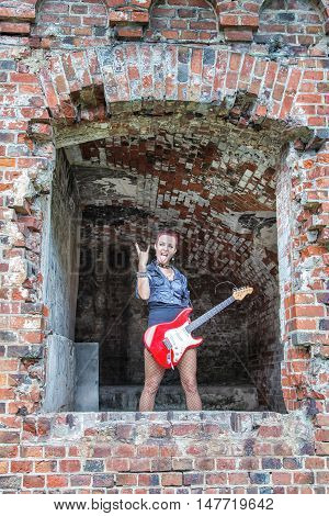 punk girl with red electric guitar standing in the window of hte abandoned castle