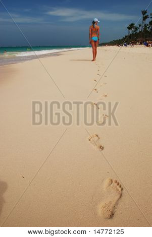 Footprints in the sand on caribbean beach. Focus on first step.