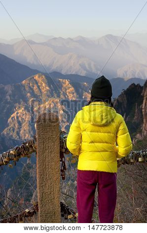 A Chinese woman wearing a winter jacket looking over the morning view of Yellow Mountain in Anhui Province China.