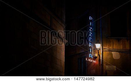 Pisa Italy - July 27 2016. Pizzeria neon sign in a italian street at night. Pisa Tuscany. Italy.