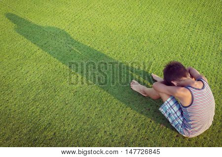 Sad lonely kid on green meadow
