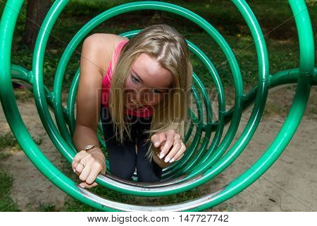 The girl laughs in a pipe to a ladder on a training apparatus in park