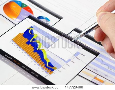 Male Hand with Pen on the Investment Charts