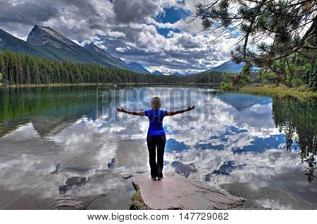 Woman by alpine lake with mountains and clouds reflection.  Honeymoon lake. Banff National Park. Canadian Rockies. Alberta. Canada.