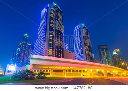 DUBAI, UAE - MARCH 30, 2014: Illuminated skyscrapers of Dubai Marina at night, United Arab Emirates. Dubai Marina is a district with artificial canal city who accommodates more than 120,000 people.