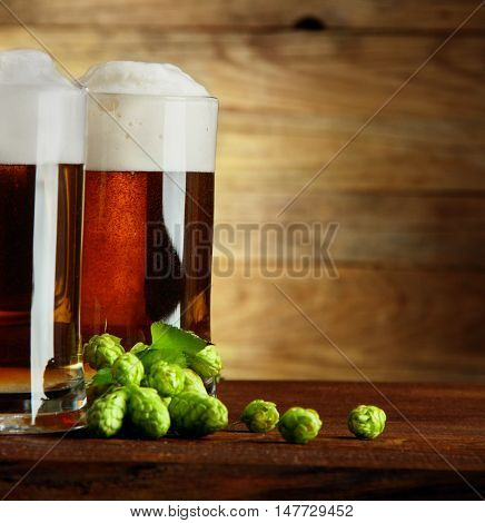 Two mugs of beer and hop on a wooden table.Vertical shot