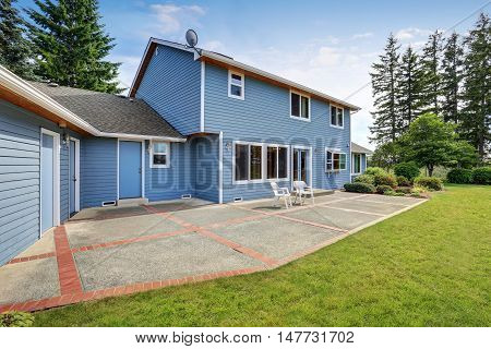 Blue House Backyard With Concrete Floor Patio Area And Well Kept Garden.