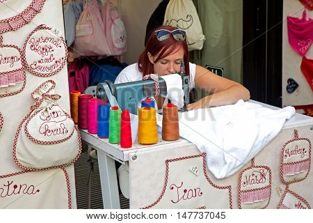 Ljubljana Slovenia Aug 25 2016: Young girl using sewing machine for handmade customized souvenirs