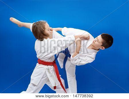 Young athletes train blocks and kicks of karate