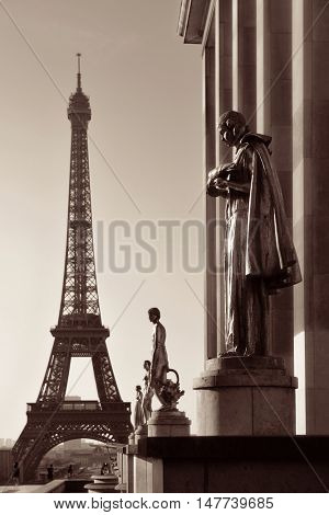 Eiffel Tower with statue as the famous city landmark in Paris