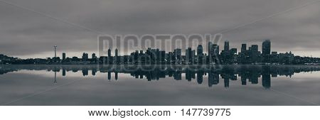 Seattle city skyline view over sea at sunrise with urban architecture and reflection.