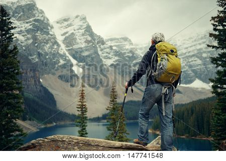 Hiker in Moraine Lake with snow capped mountain of Banff National Park in Canada