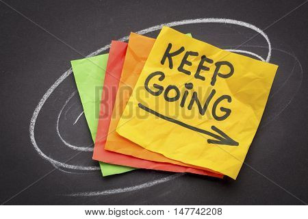 keep going - motivation or determination concept - handwriting on colorful sticky notes against black paper