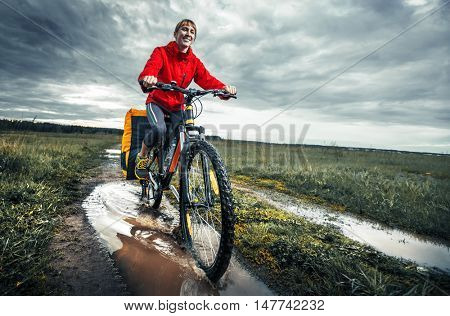 Young lady hiker with loaded bicycle riding through the puddle on a wet rural road