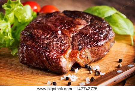 grilled rib-eye steak with herbs on wooden background