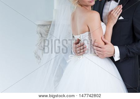 bride and groom embrace on wedding day