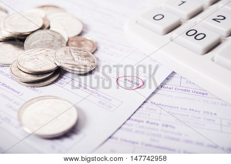 Utility bill with silver coins and calculator save money concept