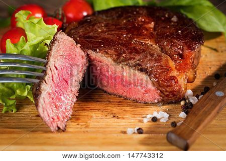 medium roast rib-eye steak on wooden plate with pepper and salt