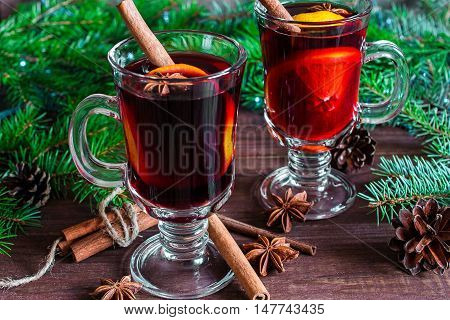 two glasses of hot christmas mulled wine with christmas tree pine cones on wooden background