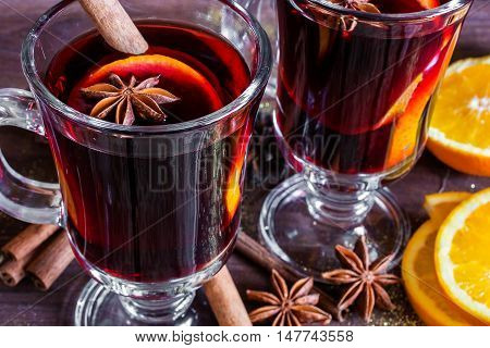 two glasses of hot mulled wine with spices and sliced orange on wooden background. close up