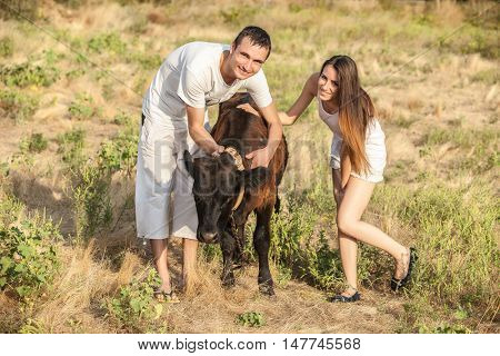 young couple of farmers with a bull-calf