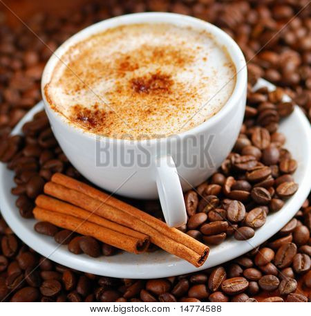Cup of cappuccino  with cinnamon and spilled out coffee beans.