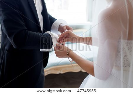 The bride helps her fiance to fasten cufflinks. Wedding worries. Close-up