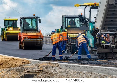 Close view on the workers and the asphalting machines