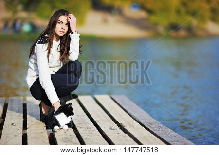 Beautiful young brunette girl in the white sweater stroking a cat on street wooden walkways near the lake. Lifestyle love to pets.