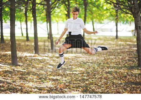 Sport and lifestyle concept - girl jumping outdoors in autumn park