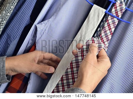 closeup of a young caucasian man choosing a tie from the closet
