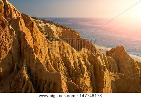 Sharp and steep cliffs near a beach under sunset warm light