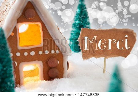 Gingerbread House In Snowy Scenery As Christmas Decoration. Trees And Candlelight For Romantic Atmosphere. Silver Background With Bokeh Effect. French Text Merci Means Thank You