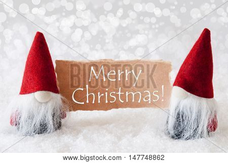 Christmas Greeting Card With Two Red Gnomes. Sparkling Bokeh Background With Snow. English Text Merry Christmas