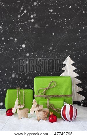 Green Gifts Or Presents With Christmas Decoration Like Tree, Moose Or Red Christmas Tree Ball. Black Cement Wall As Background With Snow. Vertical Christmas Greeting Card With Snowflakes