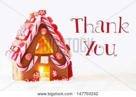 Gingerbread House In Snowy Scenery As Christmas Decoration With White Background. Candlelight For Romantic Atmosphere. English Text Thank You