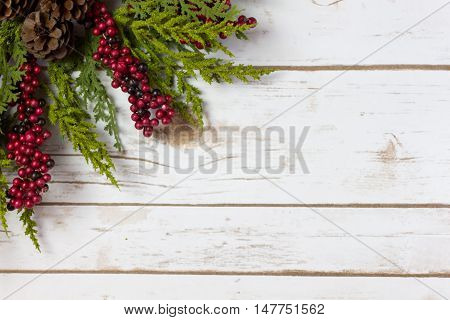 Christmas Garland with Pine Cones and Berries on a white wood plank board with room for writing or text in the background