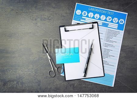 Medical concept. Clipboard, business card with laboratory tests form and scissors on gray background