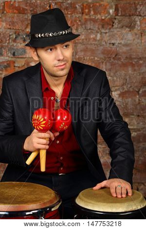 Handsome man in suit and hat poses with maracas and drums in studio with brick wall