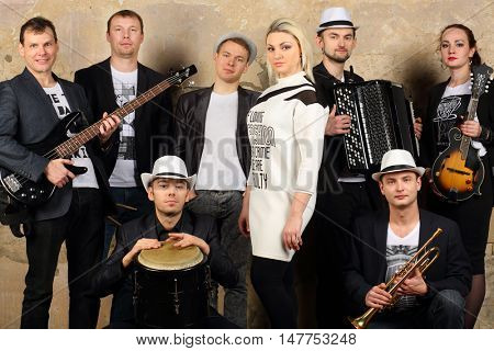 Music band of eight young people in white and black clothes pose in studio