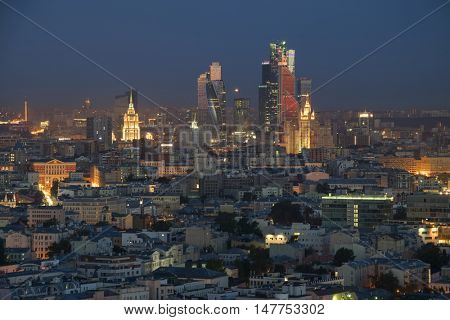Residential buildings, roofs and skyscrapers at summer night in Moscow, Russia