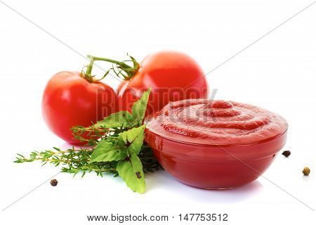 Glass bowl of ketchup or tomato sauce with ingredients tomatoes, basil, thyme, pepper isolated on white background