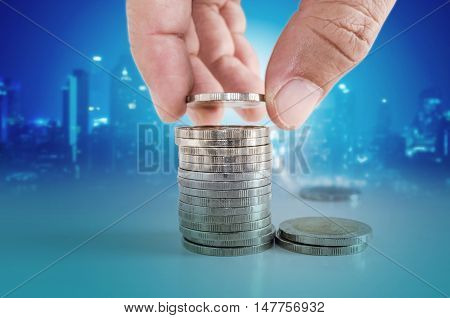 Saving Money Concept. Hand Putting Coin To Stacks Of Coins.