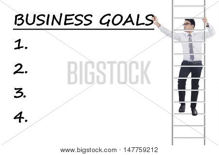 Young businessman climbing a ladder and write business goals isolated on white background