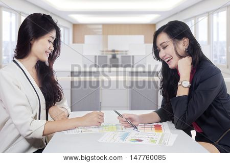Two beautiful businesswomen working in the office while discussing with financial chart on the table
