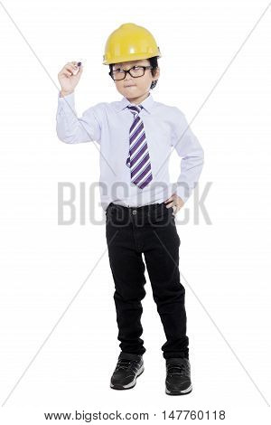 Full length of schoolboy standing in the studio while wearing helmet and writing something on transparent whiteboard
