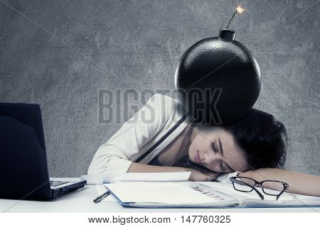Young woman sleeping on the table with document and bomb above her head