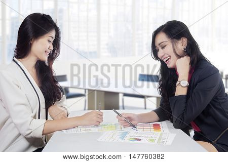 Image of two young businesswoman discussing together with document of financial chart on desk